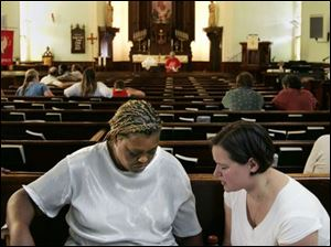 Cheryl Jeffries, left, prays with pastoral intern Abby D Ambruoso at Salem Lutheran Church.