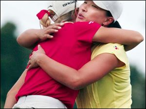 Natalie Gulbis, left, gives Se Ri Pak a hug after they finished the first round of the Farr Classic at Highland Meadows.
