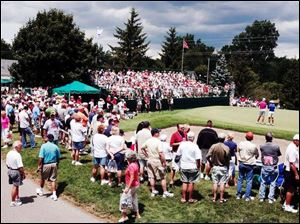 Fans watch the action at the No. 9 green yesterday in the opening round of the Farr Classic.