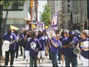 Union members march on Madison Avenue to support wages in line with those in other cities.