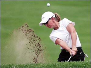 Carri Wood blasts out of a trap on the fifth hole, where she got a double bogey, but she finished 1-under for the day.