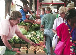 Eleanor Billau of Bedford Township sets out some fresh and tempting vegetables for visitors to the Toledo Farmer's Market.