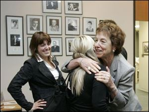 Student Agnes Keszi gets a good-bye hug from Lynn Jacobs, assistant prosecutor, while Melinda Lanczi looks on.