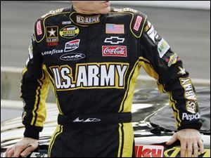 Driver Mark Martin whiles away the time yesterday while waiting to qualify for today s Allstate 400 in Indianapolis.