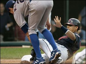 The Indians  Victor Martinez tries to score, but he is tagged out by Rangers pitcher Brandon McCarthy in the fourth inning.