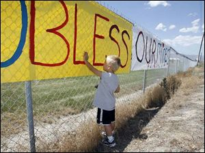 Wylee Sherman, 3, puts a painted handprint to a poster, put up in support of the trapped miners, in Huntington, Utah on Tuesday.