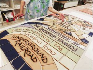 Sister Jane Mary Sorosiak, adjunct art instructor at Lourdes College in Sylvania, inserts the last piece into a ceramic mural she has made for the Lathrop House celebrating its role as a stop on the Underground Railroad. The Franciscan nun has created murals a