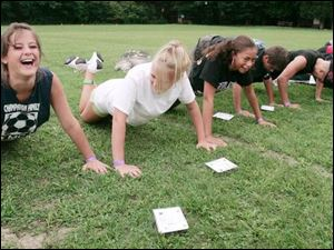 From left, Taylor Deady of Cable, Ohio, Samantha Dunn of Chillicothe, Ohio, and Rachel Harris of Columbus find push-ups are more fun if they have a sense of humor during Operation: Military Kids.