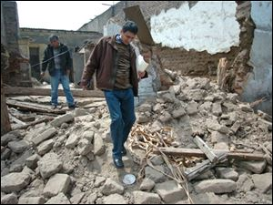 Members of the Peruvian Civil Defense inspect a building damaged during Wednesday's earthquake.