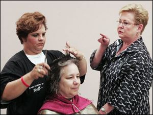 Sherry Smith, left, cuts Lynne Michalak's hair u