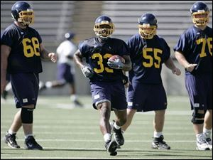 Toledo running back Jalen Parmele (33) works out with linemen, from left, Jared Dewalt, Levi George and Kevin Kilgo.