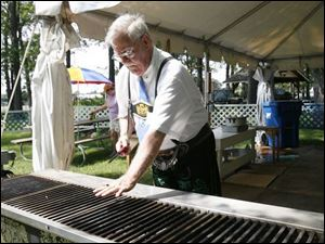 Lou Shindledecker checks the grill to see if it's time to put on the bratwurst he hopes to sell to visitors.
