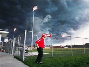 Jim Stover is the last person to leave the field as a storm looms over Rogers High School.