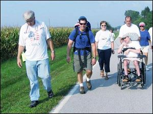 Author Jeff Alt has daughter, Madison, on his back as he walks with stepmother Sue Alt; his father Mike pushes Jeff s brother, Aaron, in a wheelchair, all for the annual Walk with Sunshine.