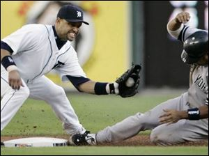 The Yankees  Bobby Abreu beats the tag of the Tigers  Placido Polanco in the first inning of last night s game.