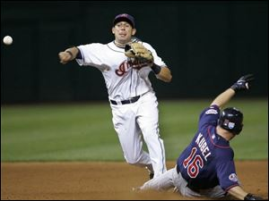 The Indians' Asdrubal Cabrera throws to first to get the Twins' Mike Redmond to complete a triple play. It was the Indians' first triple play in Cleveland since they did it in 1976.