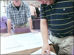 Willy van Bakel, left, and Charles Bryan of Wauseon Downtown Development talk over a proposed project consisting of a hotel and shops to replace that portion of the city's downtown that was destroyed by fire in April.