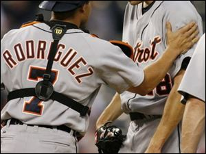 Catcher Ivan Rodriguez consoles departing Tigers pitcher Andrew Miller after he was stung with five earned runs in the first inning.