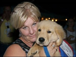 Jenni Yoder with a puppy at the Dealin  For Dogs fund-raiser.