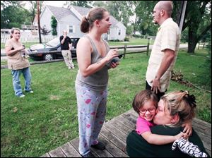 Makayla Machcinski gets a hug from neighbor Pam Davis while her mom, Shiloh, and uncle, Randy Logan, stay close at hand.