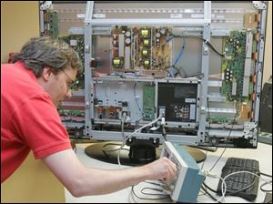 Jeff Guy runs tests on a flat-panel display at Imaging Systems Technology Inc., a Toledo company that received state grants in 2004 and 2005 totaling nearly $800,000.