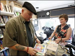 Librarians Chris Spradlin and Marilyn Howard check books at the bookmobile, which is being used while the main library is renovated as a result of last month s flooding in Findlay.