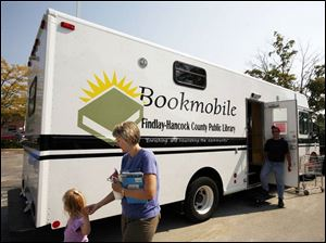 Heidi Rupp and her daughter, Megan, 3, of Findlay leave the bookmobile that serves in place of the main Findlay-Hancock County Library, which has been closed since the flooding.