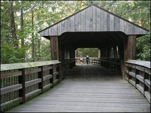 Wildwood Preserve Metropark in Toledo gained this 60-foot Howe truss covered footbridge over the Ottawa River in 2002, linking original and new sections of the park.