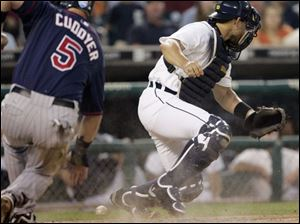 The Twins' Michael Cuddyer scores as Tigers catcher Ivan Rodriguez can't come up with Timo Perez's throw from left field.