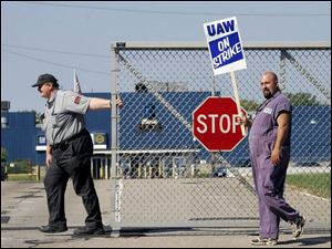 A guard closes a gate at the General Motors plant in Parma, Ohio, as autoworker Anthony Pesce pickets.