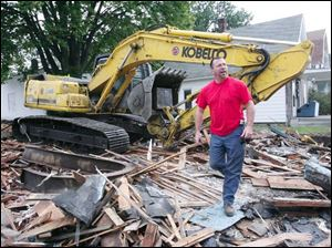 Richard Hendrickson inspects his handiwork after tearing down a nuisance property on West Central Avenue last week. Known as 'the King' by his co-workers, Mr. Hendrickson says it's sad to see buildings be-come neglected, but he takes