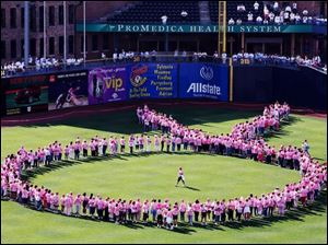 Cancer survivors form a pink ribbon at Fifth Third Field.