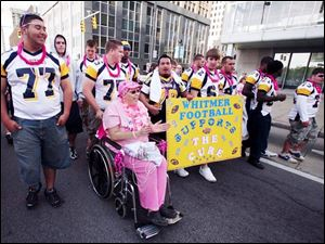 Members of the Whitmer High School football team push Candace Meridieth of West Toledo. Ms. Meridieth was diagnosed with cancer last spring and covered the 3.1-mile course in a wheelchair.