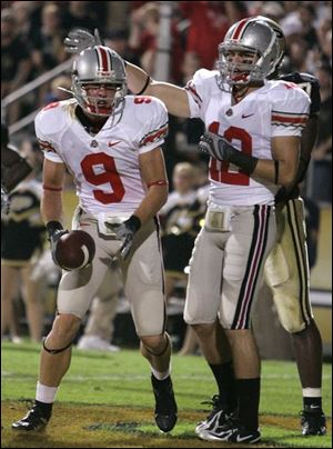 Ohio State wide receiver Brian Hartline, left, is congratulated by Dane Sanzenbacher after scoring a touchdown in the first quarter last night against Purdue.