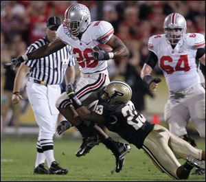 Ohio State running back Chris Wells tries to pull away from Purdue's Justin Scott in the first quarter last night. Wells gained 85 yards on 18 carries as the Buckeyes dealt the Boilermakers their first loss of the season.