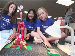 Elizabeth Sares, Michelle Li, and Jordan Truitt, all 12, work on a solar-powered toy at Sylvania's Timberstone Junior High as part of an energy-conservation awareness project.