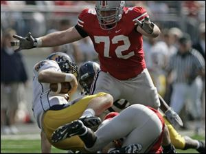Ohio State defensive tackle Dexter Larimore is about to pounce on Kent State's quarterback.