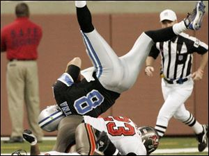 The Lions' Jon Kitna, a throwback quarterback, was upended by the Bucs defense but his scramble earned a first down.