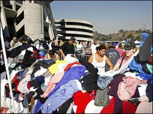 People displaced by the fires search through piles of donated clothing outside Qualcomm Stadium in San Diego. Thousands of evacuees took shelter at the stadium, home of the NFL s San Diego Chargers.