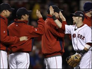 Boston Red Sox second baseman Dustin Pedroia, second left, is congratulated by his teammates after their 13-1 victory over the Colorado Rockies in Game 1 of the baseball World Series Wednesday, Oct. 24, 2007, at Fenway Park in Boston.