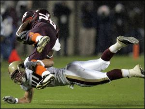 Boston College s Jamie Silva dives to tackle Virginia Tech tailback Brandon Ore with one arm.