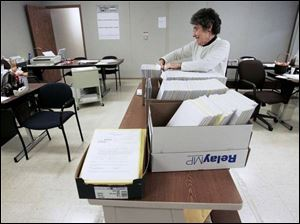Hancock County Board of Elections clerk Donna Spitler sorts through more than 2,000 absentee ballots in the board's temporary headquarters. Last summer's flooding destroyed about 91 of the county's 300 voting machines.