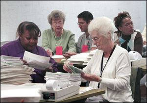 Yolanda Riggs, left, and Betty Brown prepare absentee ballots to be counted at the Lucas County