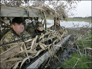 James Donnell Konkel, left, Heather Braun and Kent Felbinger keep watch over Rusk Marsh on Sandusky Bay hoping to get a shot off during a day of duck hunting recently.