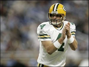 Green Bay quarterback Brett Favre claps after Greg Jennings grabbed a four-yard TD pass in the third quarter at Detroit.