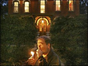 Current owner Tim Mussard lights up a cigar in front of his 1870 mansion in Berea, Ohio. Mr. Mussard and his wife, both singers, intend to hold concerts in the downtown mansion. the plain dealer The Berea mansion, which was nearly destroyed by fire, features brick and stonework.