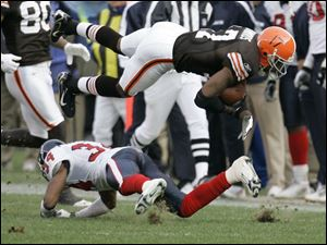 The Browns' Braylon Edwards has his feet taken out by the Texans' Von Hutchins.