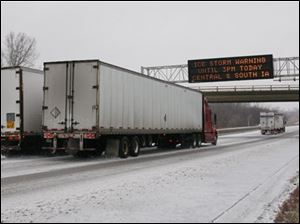 Trucks pass under a message board on westbound Interstate 80 indicating an ice storm warning near Des Moines, Iowa, on Saturday, Dec. 1, 2007.
