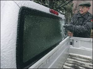 Tom Benecke, a Government Center security guard, scrapes a truck window in a chilly task necessitated by the storm.