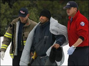 Frederick Dominguez, center, is helped to an ambulance after being rescued with his three children by a California Highway Patrol helicopter.